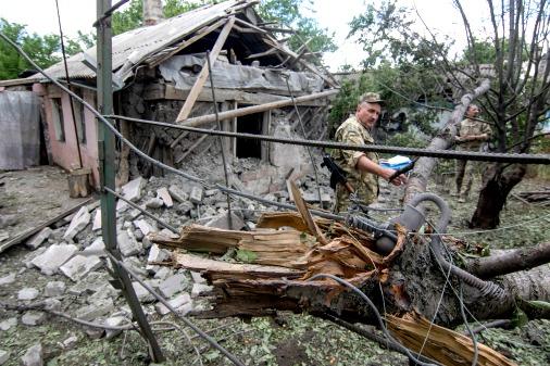 Иллюстративное фото. Украинский военный рассматривает разрушения в деревне Ольгинко, июнь 2017 года
