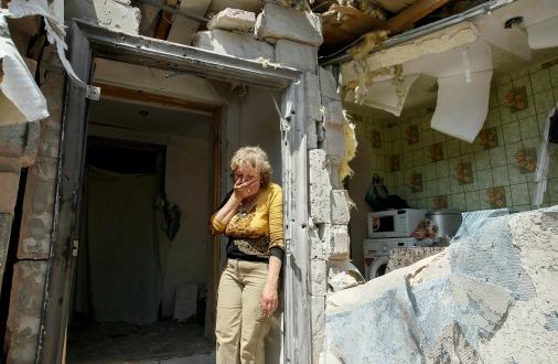 Женщина на развалинах своего дома в районе АТО неподалеку от Донецка, май 2016